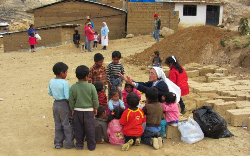 Suora con bambini in Perù
