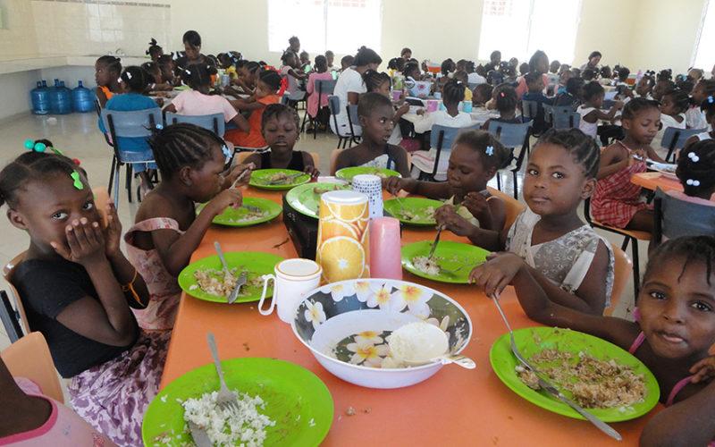 Bambini in una mensa ad Haiti mentre mangiano del riso
