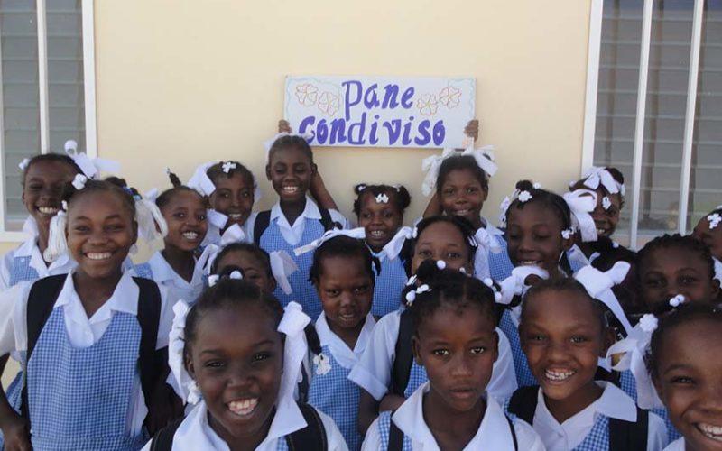 Gruppo di bambine con in mano cartello con scritto Pane Condiviso