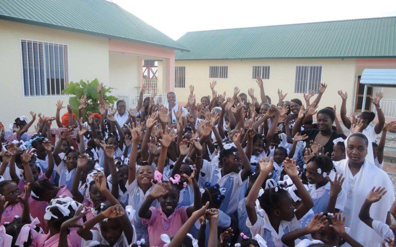 gruppo di bambine e ragazze haitiane con le braccia alzate