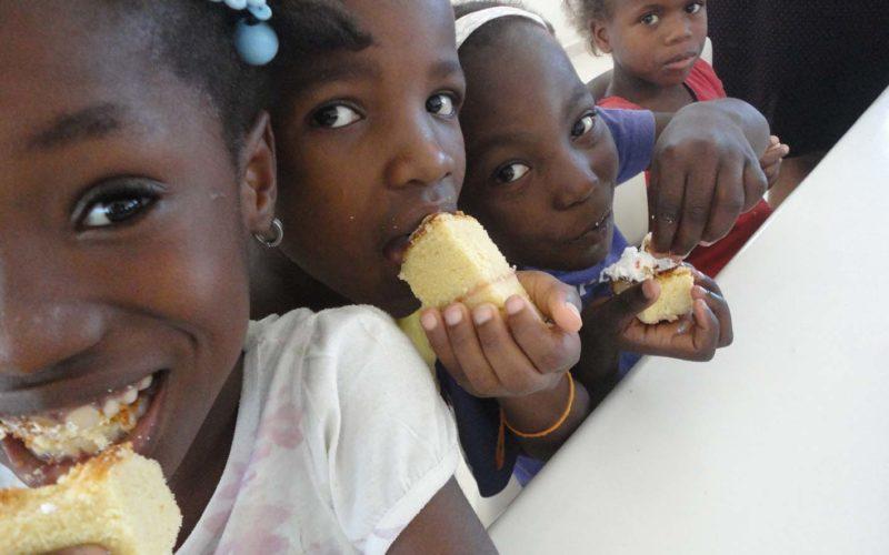 Bambine mentre mangiano una torta