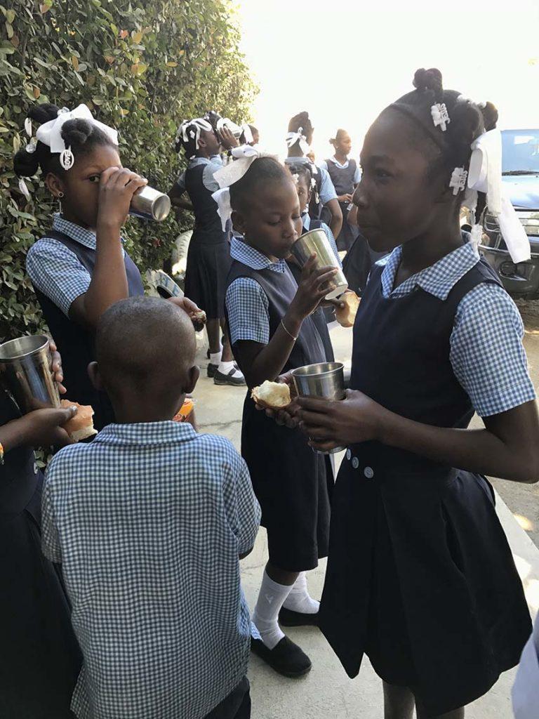 bambini di Haiti mangiano pane e bevono acqua